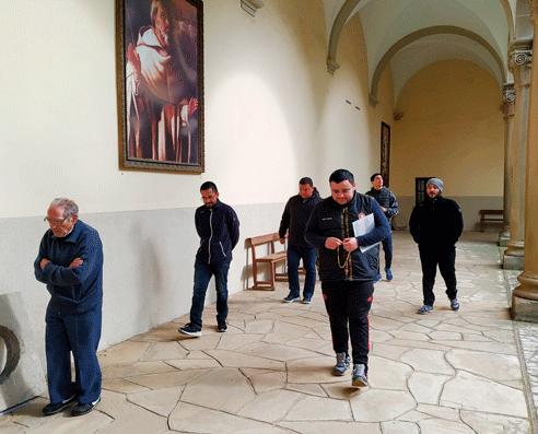 Novicios y religiosos del Noviciado de San Ramón, rezando juntos el Santo Rosario en los pasillos del claustro.